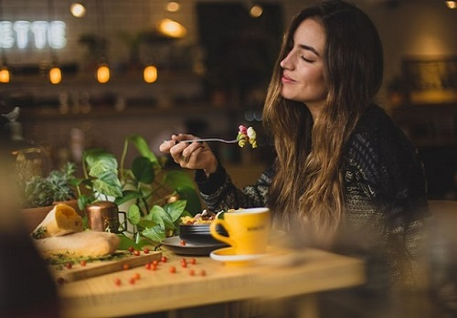 Woman enjoying a meal with a food intolerance